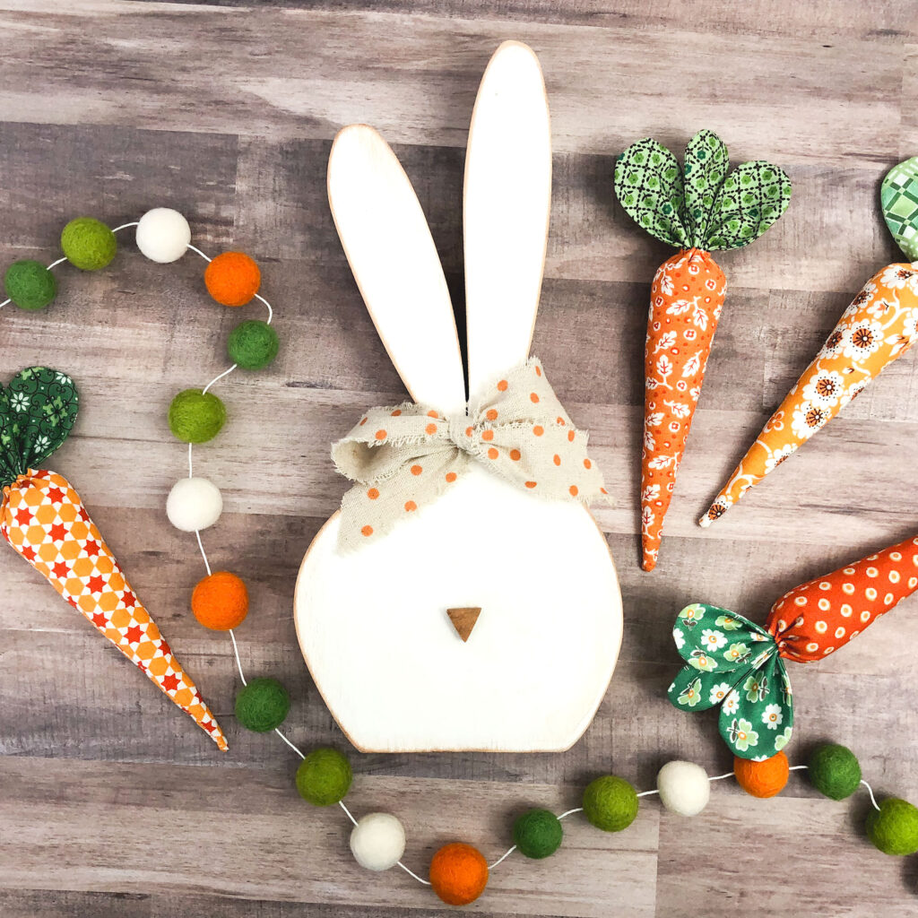 How to sew fabric carrots with top US sewing blog Ameroonie Designs. Image of wooden bunny with fabric carrots and felt pom garland.