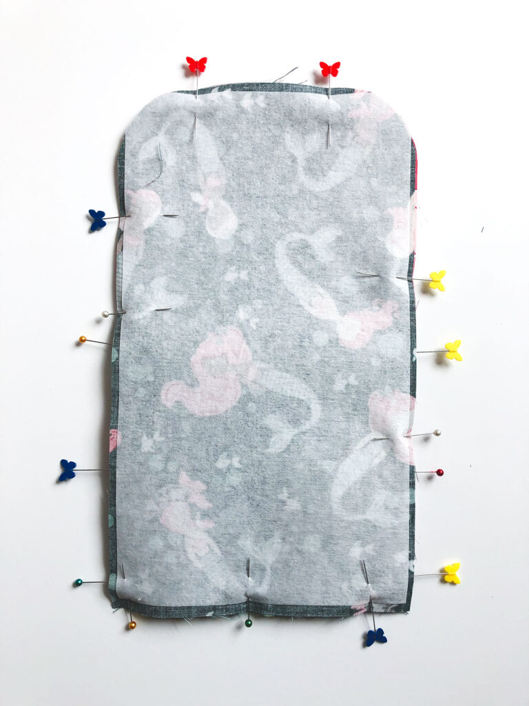 Sew a beautiful colored pencil pouch with top US sewing blog Ameroonie Designs. Image of pinning both sides of pouch together to prepare for sewing.