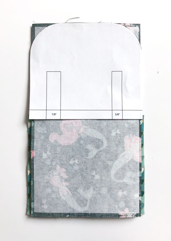 Sew a beautiful colored pencil pouch with top US sewing blog Ameroonie Designs. Image of using template to round corners of fabric pieces to create flap for colored pencil pouch.