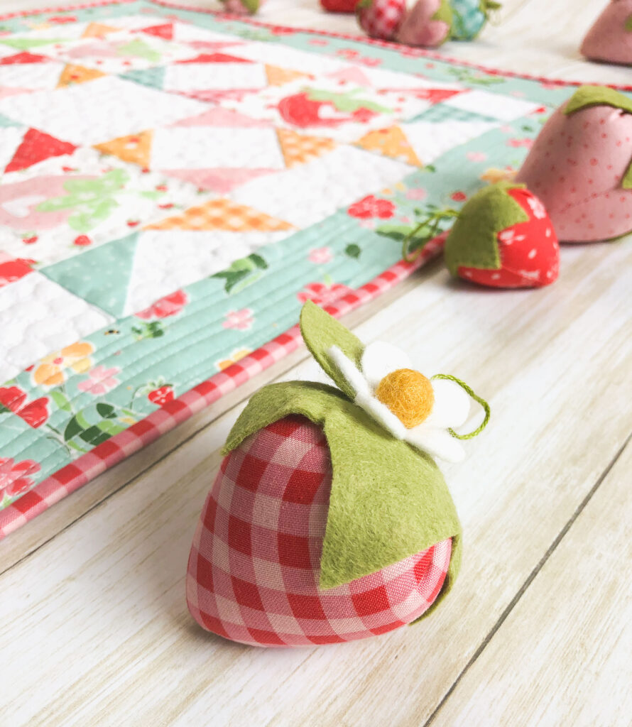 Strawberry Springtime mini quilt free pattern by top US sewing blog Ameroonie Designs. Image of stuffed fabric strawberry with mini quilt and more strawberries in background.