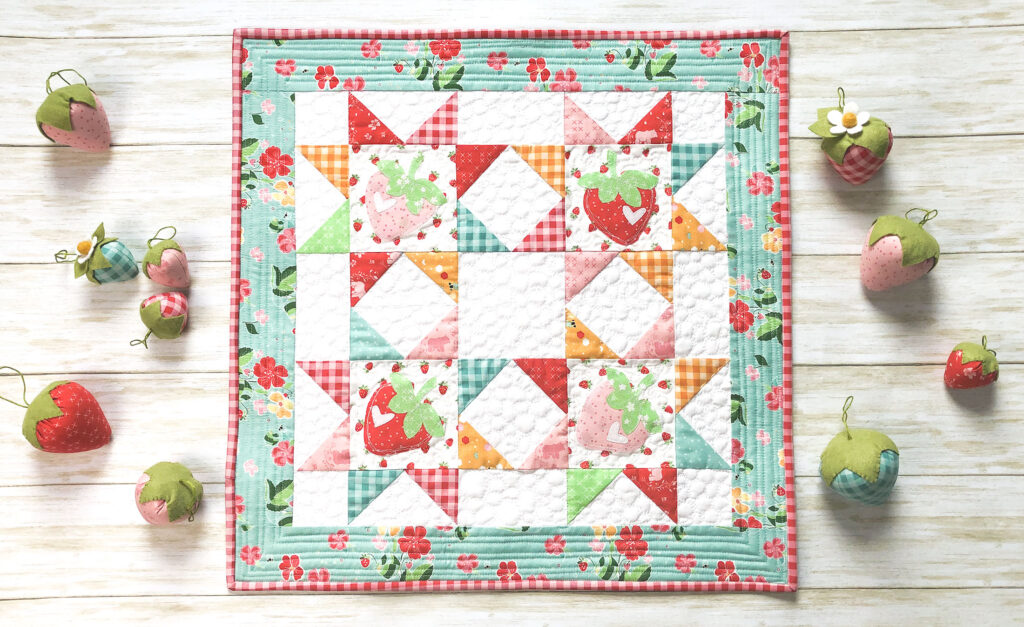 Strawberry Springtime mini quilt free pattern by top US sewing blog Ameroonie Designs. Image of mini quilt with strawberry applique and stuffed fabric strawberries.