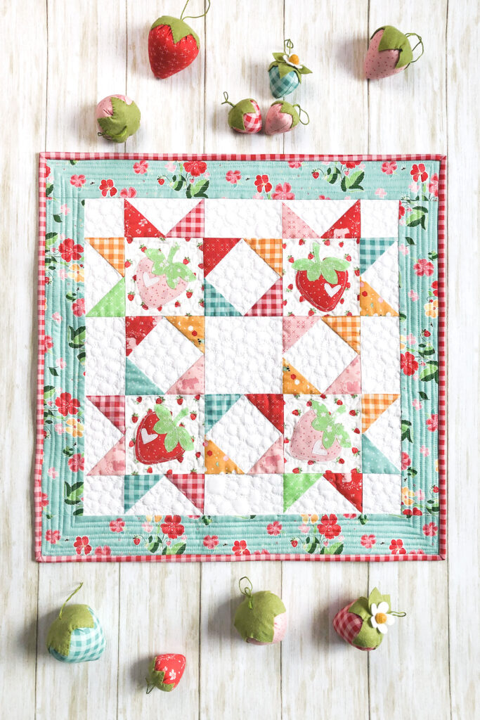 Strawberry Springtime mini quilt free pattern by top US sewing blog Ameroonie Designs. Image of strawberry springtime mini quilt with stuffed strawberries.