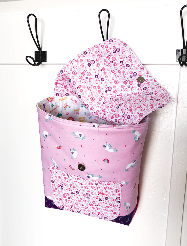 Sew an adorable backpack by top US sewing blog Ameroonie Designs. Image of pink unicorn backpack hanging from hook.