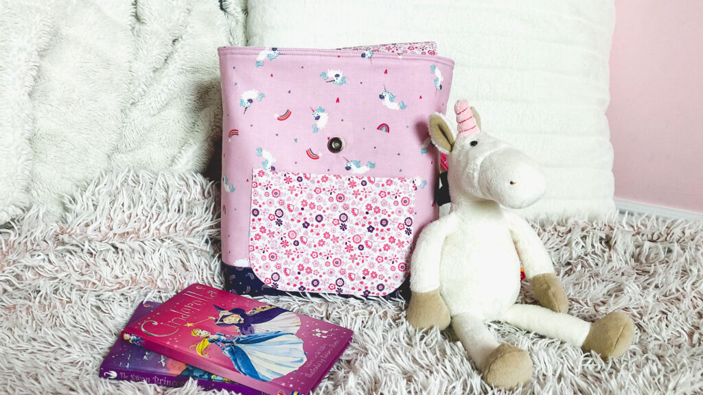 Sew an adorable backpack by top US sewing blog Ameroonie Designs. Image of pink backpack with stuffed unicorn, pillow and books.