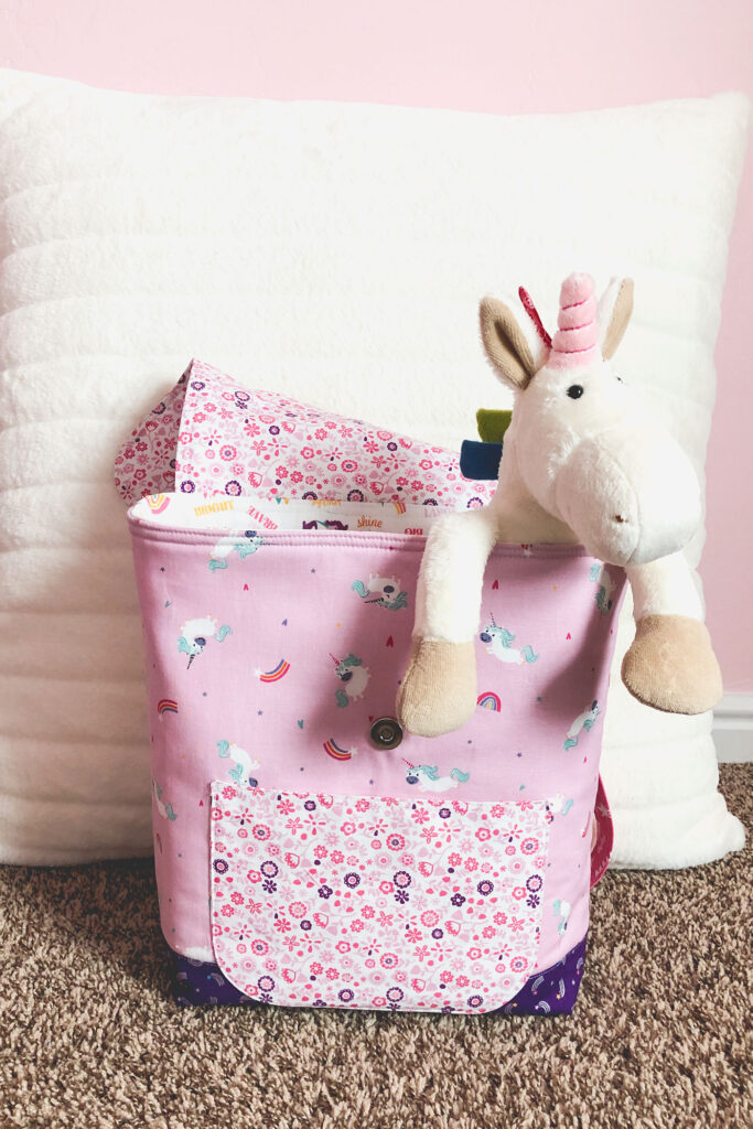 Sew an adorable backpack by top US sewing blog Ameroonie Designs. Image of stuffed unicorn hanging out of pink backpack.