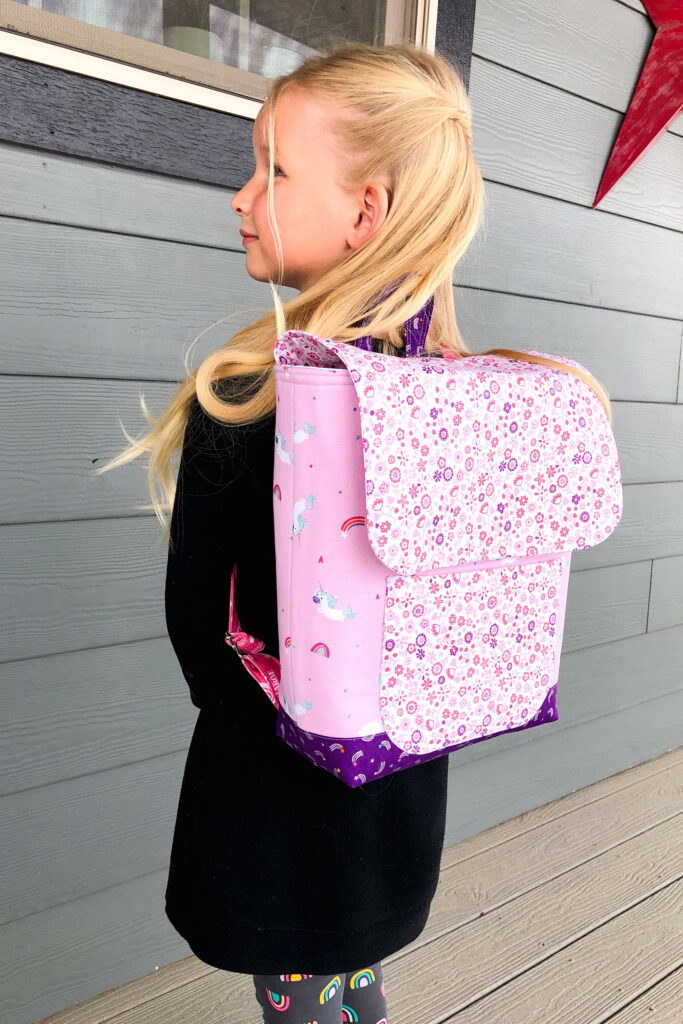 Sew an adorable backpack by top US sewing blog Ameroonie Designs. Image of girl wearing pink backpack.