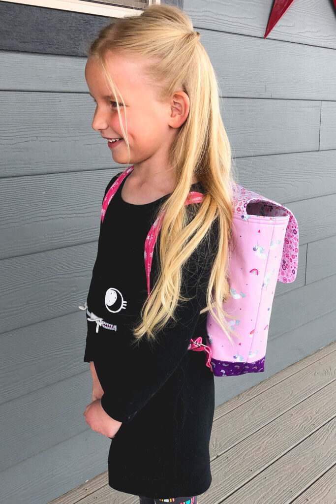 Sew an adorable backpack by top US sewing blog Ameroonie Designs. Image of girl wearing unicorn backpack.