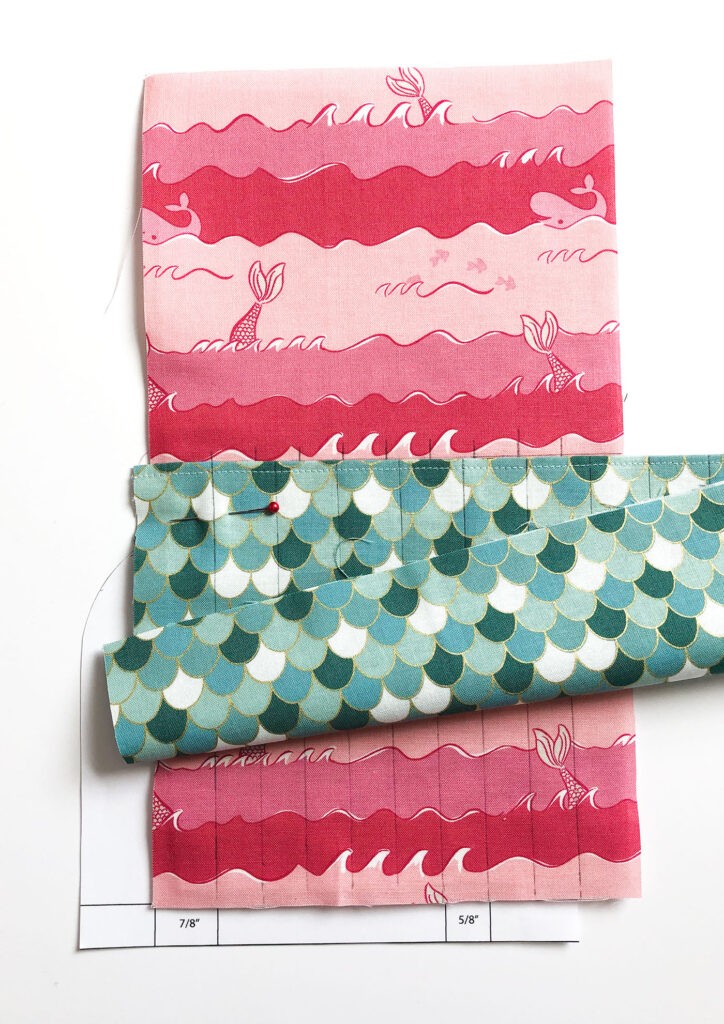 Sew a beautiful colored pencil pouch with top US sewing blog Ameroonie Designs. Image of lining up first pocket marks to create pencil pockets.