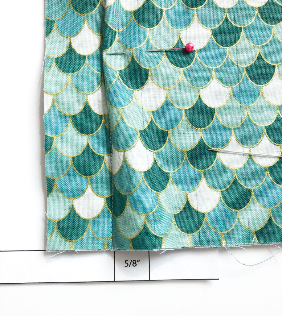 Sew a beautiful colored pencil pouch with top US sewing blog Ameroonie Designs. Image of using template to line up bottom of second side of pencil pocket.
