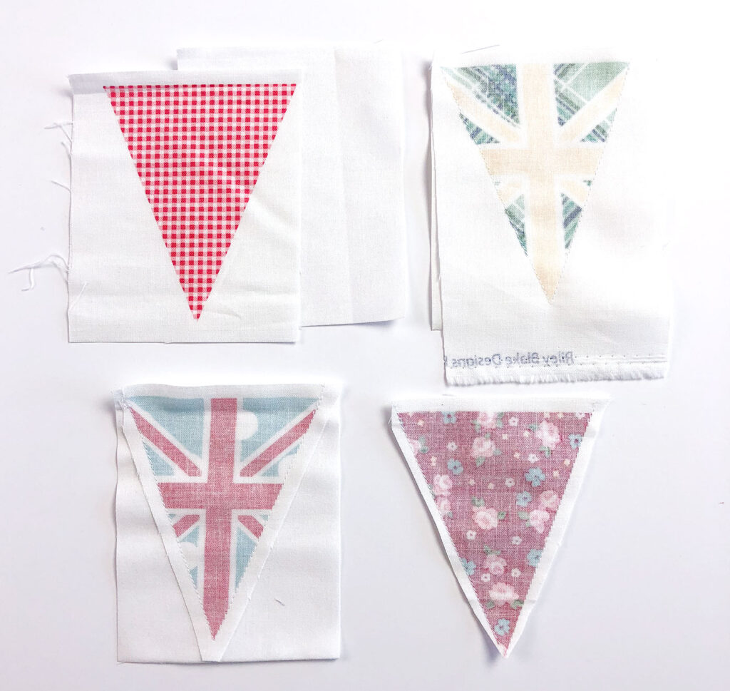 Two ways to sew a beautiful and simple fabric bunting with top US sewing blog Ameroonie Designs. Image of sewing fabric flag to background fabric to create finished edge bunting.