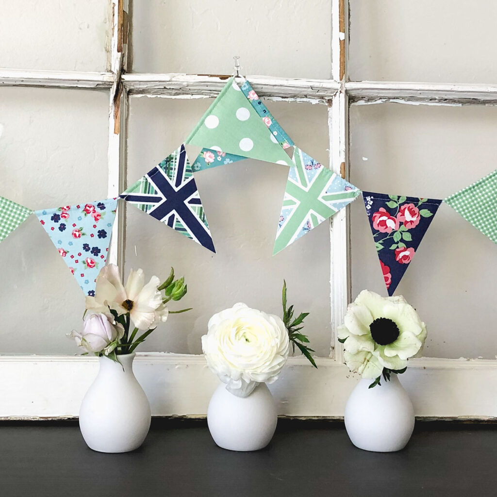 Two ways to sew a beautiful and simple fabric bunting with top US sewing blog Ameroonie Designs. Image of green and blue fabric bunting with small white flowers in bud vases.
