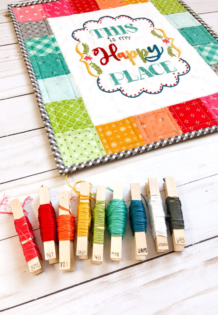 Turn your embroidery into a stunning mini quilt by Top US sewing blog Ameroonie Designs. Image of mini quilt and clothes pins with embroidery floss to show floss colors.