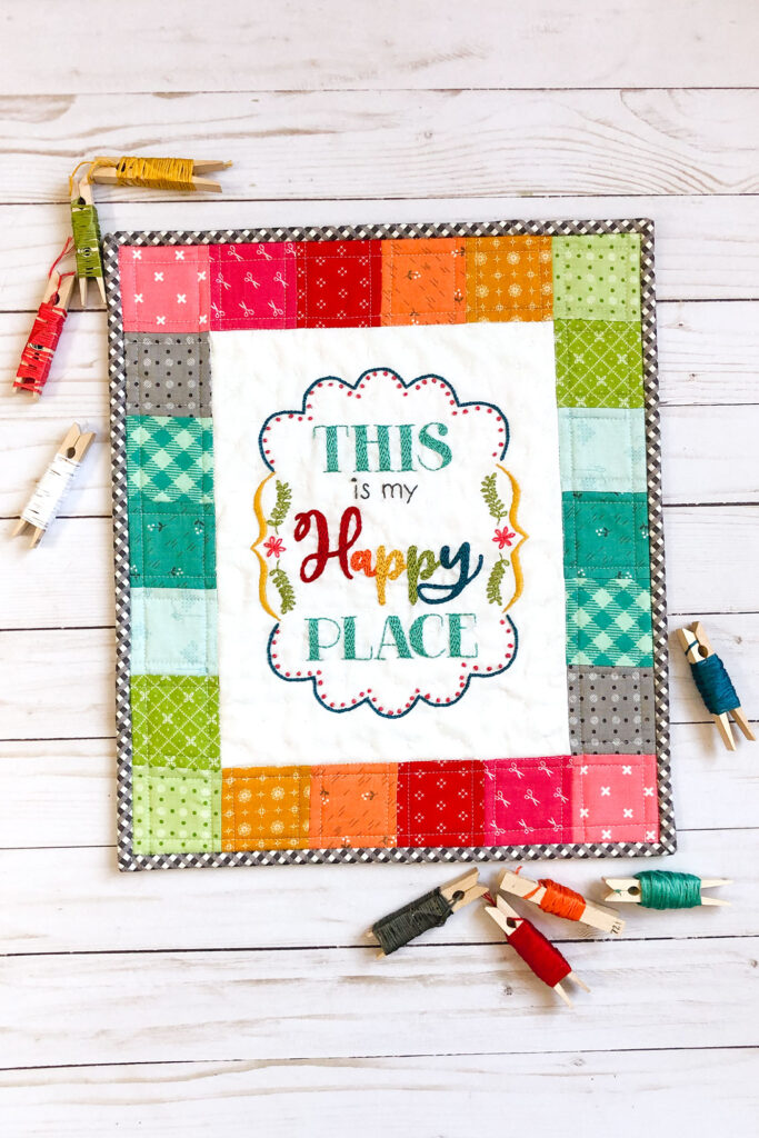 Turn your embroidery into a stunning mini quilt by Top US sewing blog Ameroonie Designs. Image of Mini quilt with embroidery and clothespins wrapped with embroidery floss.