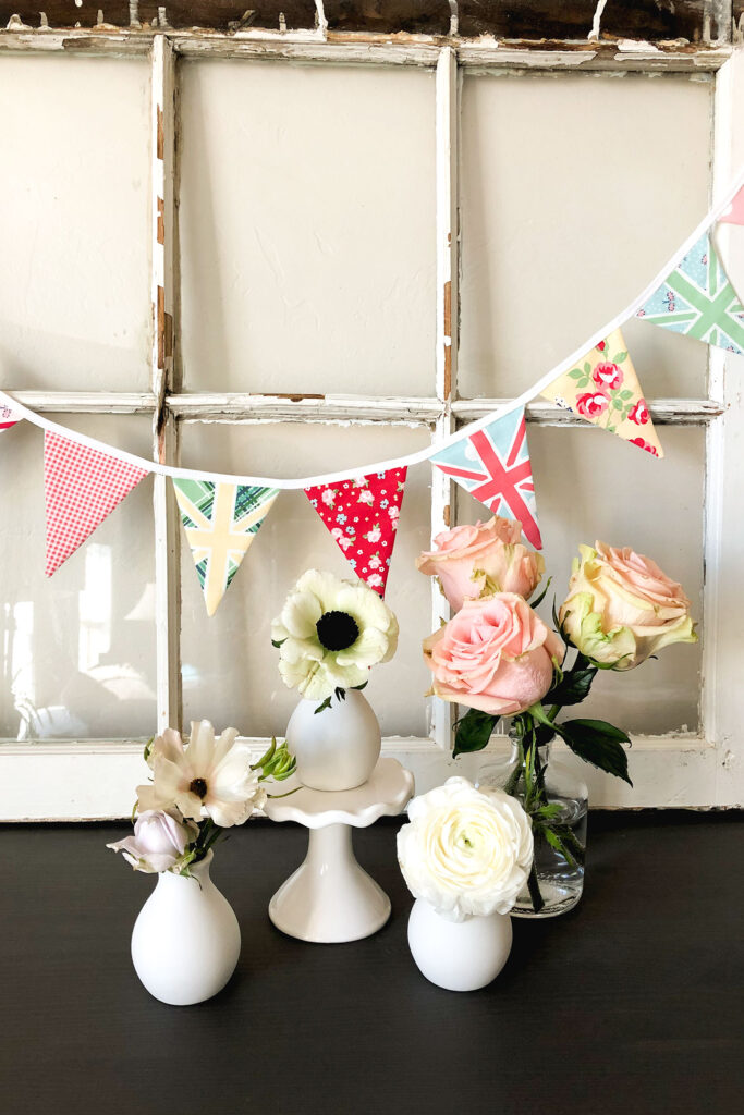 Two ways to sew a beautiful and simple fabric bunting with top US sewing blog Ameroonie Designs. Image of pink finished edge bunting with white and pink flowers in bud vases.
