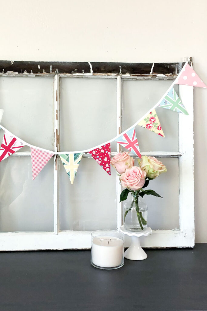 Two ways to sew a beautiful and simple fabric bunting with top US sewing blog Ameroonie Designs. Image of pink fabric bunting with pink roses in vase.