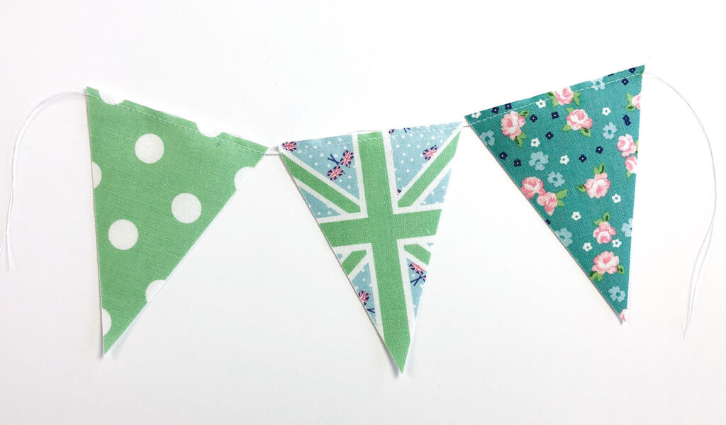 Two ways to sew a beautiful and simple fabric bunting with top US sewing blog Ameroonie Designs. Image of fabric flags simply sewn together.