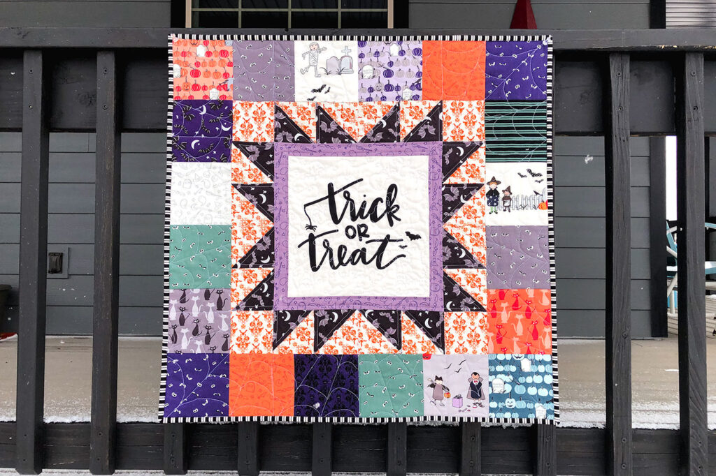 Turn a fabric panel into a stunning mini quilt from Top US sewing blog Ameroonie Designs. Image of mini quilt featuring Spooky Hollow fabric on black railing.