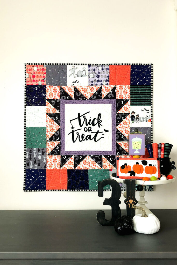 Turn a fabric panel into a stunning mini quilt from Top US sewing blog Ameroonie Designs. Image of mini quilt with Halloween decorations including mini appliqued pillow.