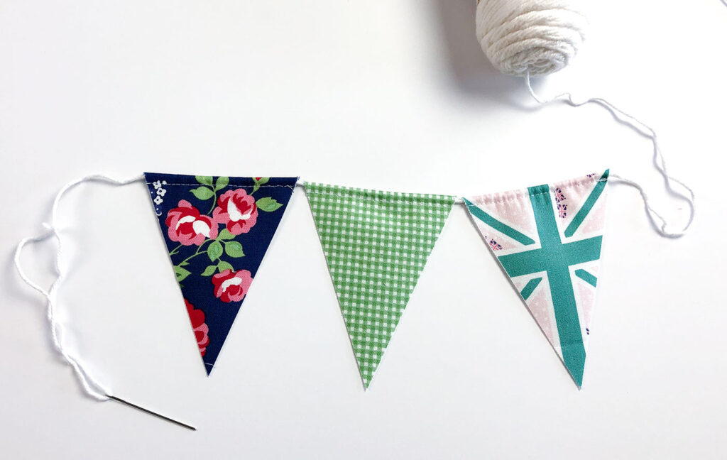 Two ways to sew a beautiful and simple fabric bunting with top US sewing blog Ameroonie Designs. Image of fabric flags on string.