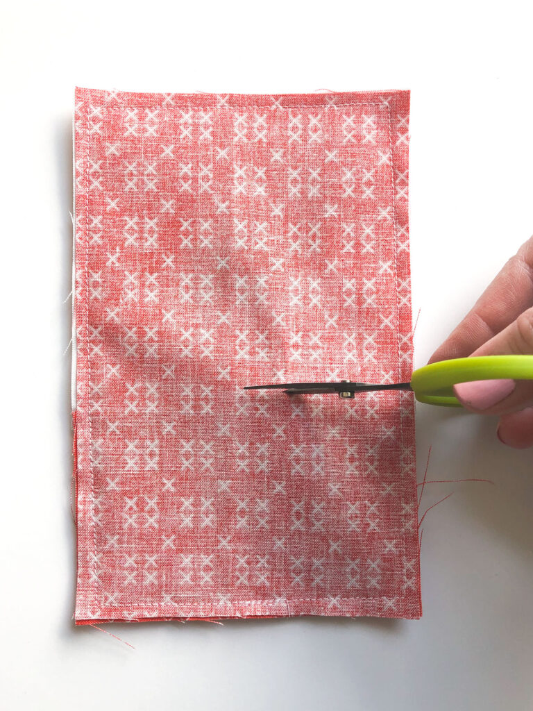 How to sew an easy embroidered strawberry mini pillow with top US sewing blog Ameroonie Designs. Image of scissors cutting slit in back of mini pillow for turning and stuffing.