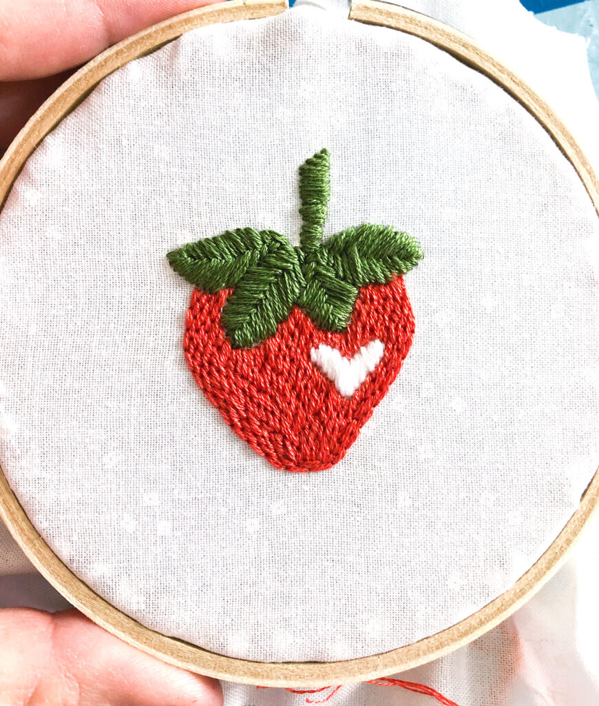 Learn how to stitch a layered back stitch. Image of strawberry embroidered with layered back stitch.
