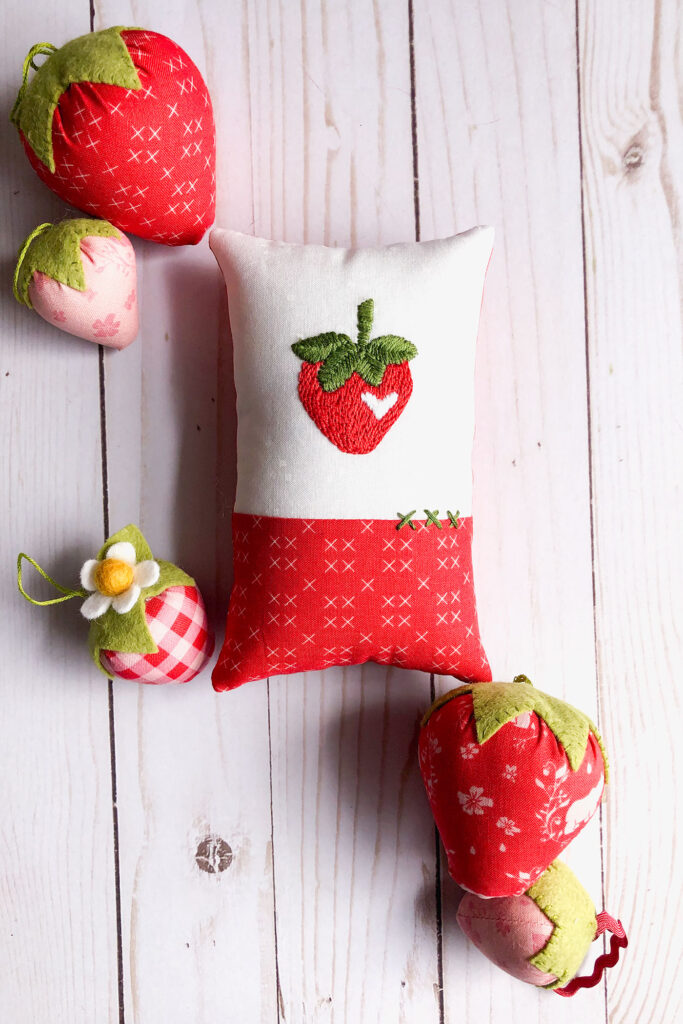 How to sew an easy embroidered strawberry mini pillow with top US sewing blog Ameroonie Designs. Image of mini pillow surrounded by fabric strawberries.