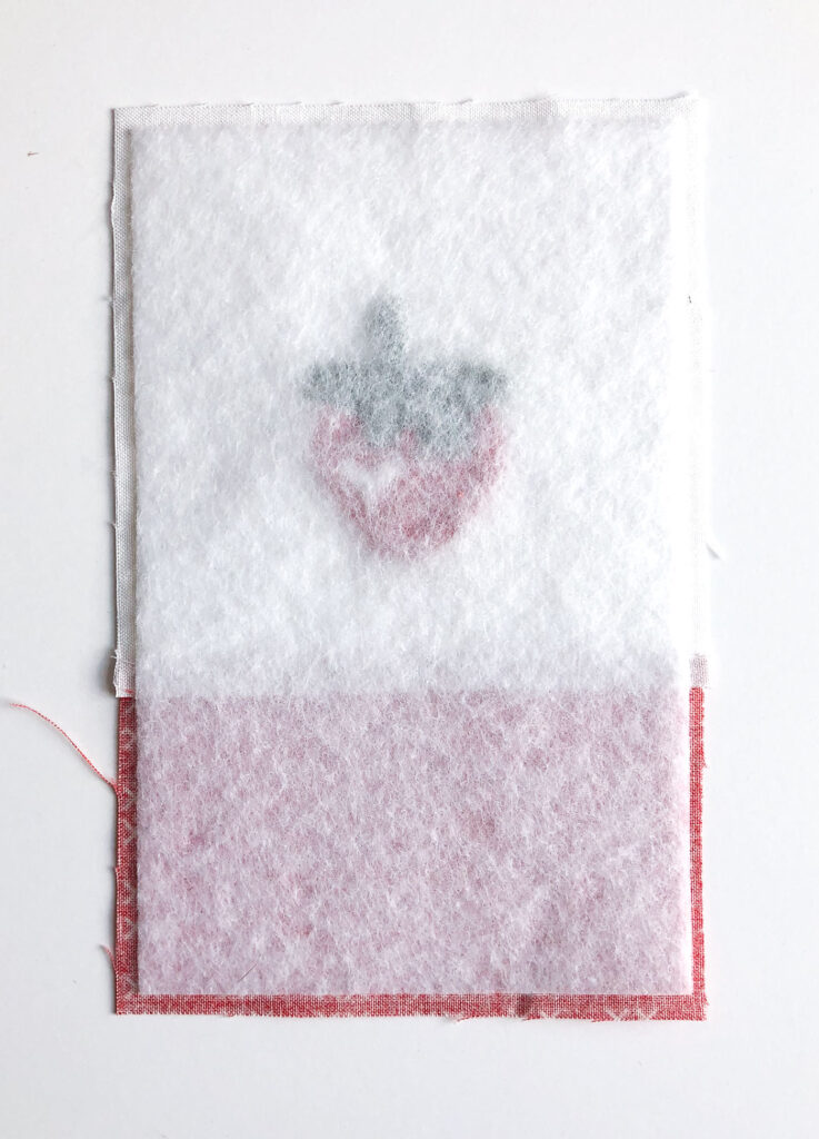 How to sew an easy embroidered strawberry mini pillow with top US sewing blog Ameroonie Designs. Image of fleece fused to back of pillow front.