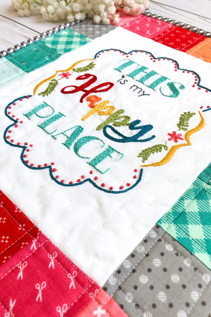 """Learn how to stitch a layered back stitch. Image of mini quilt with embroidered sentiment saying, """"This is my happy place."""""""