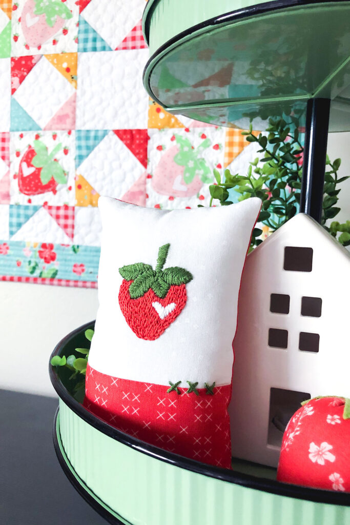 How to sew an easy embroidered strawberry mini pillow with top US sewing blog Ameroonie Designs. Image of mini pillow in tiered tray.