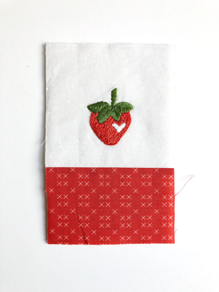 How to sew an easy embroidered strawberry mini pillow with top US sewing blog Ameroonie Designs. Image of assembly of mini pillow front.