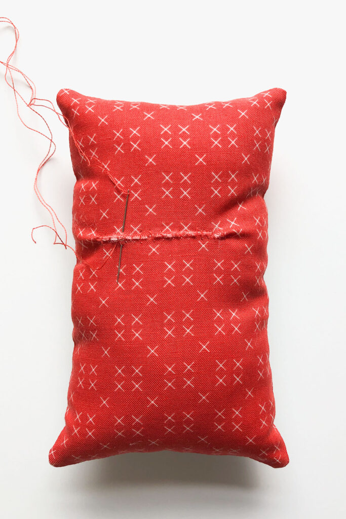 How to sew an easy embroidered strawberry mini pillow with top US sewing blog Ameroonie Designs. Image of opening in back of mini pillow being sewn shut.