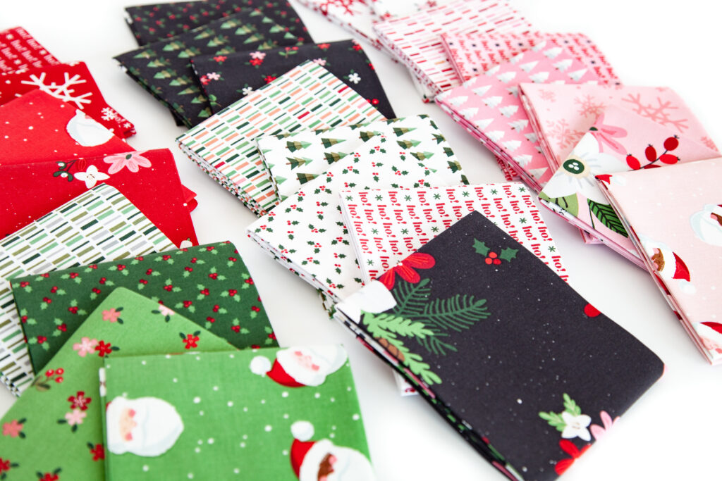How to sew a delightful holiday mini quilt by top US sewing blog Ameroonie Designs. Image of fat quarters of Holly Holiday fabric prints.