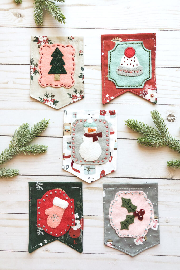 Gorgeous winter mini banner sneak peek with top US sewing blog Ameroonie Designs. Image of tree, hat, snowman, mitten and holly in wool felt applique on mini banner flags.
