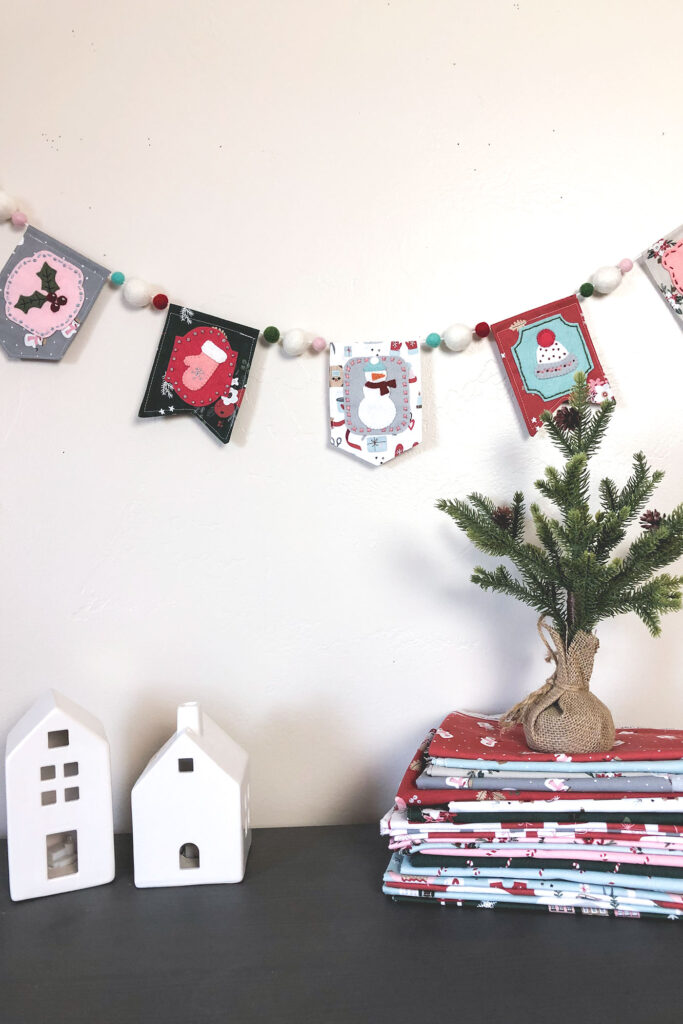 Gorgeous winter mini banner sneak peek with top US sewing blog Ameroonie Designs. Image of mini banner strung with pom poms, houses and mini pine tree.