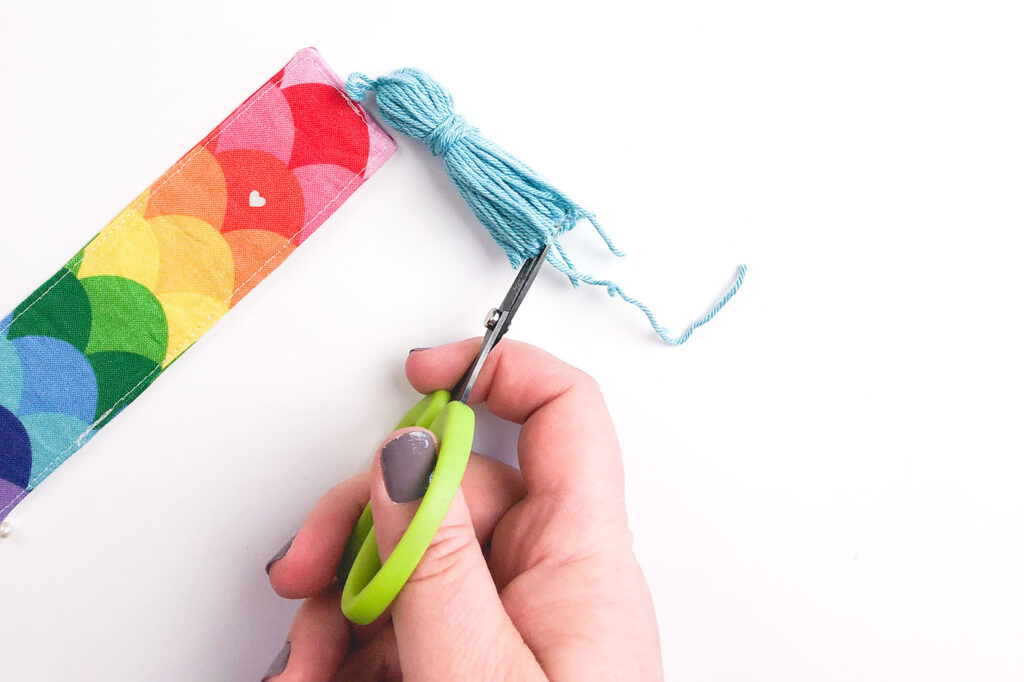 How to sew a tasseled fabric bookmark with top US sewing blog Ameroonie Designs. Image of scissors trimming the bottom of the tassel.