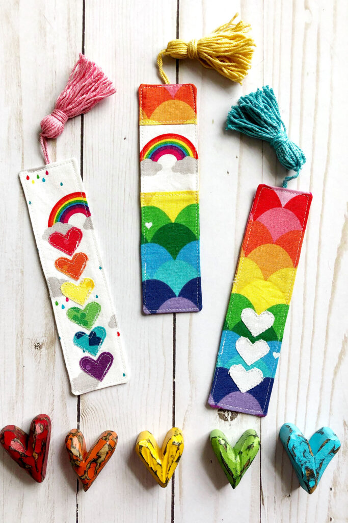 How to sew a tasseled fabric bookmark with top US sewing blog Ameroonie Designs. Image of three rainbow colored fabric bookmarks.