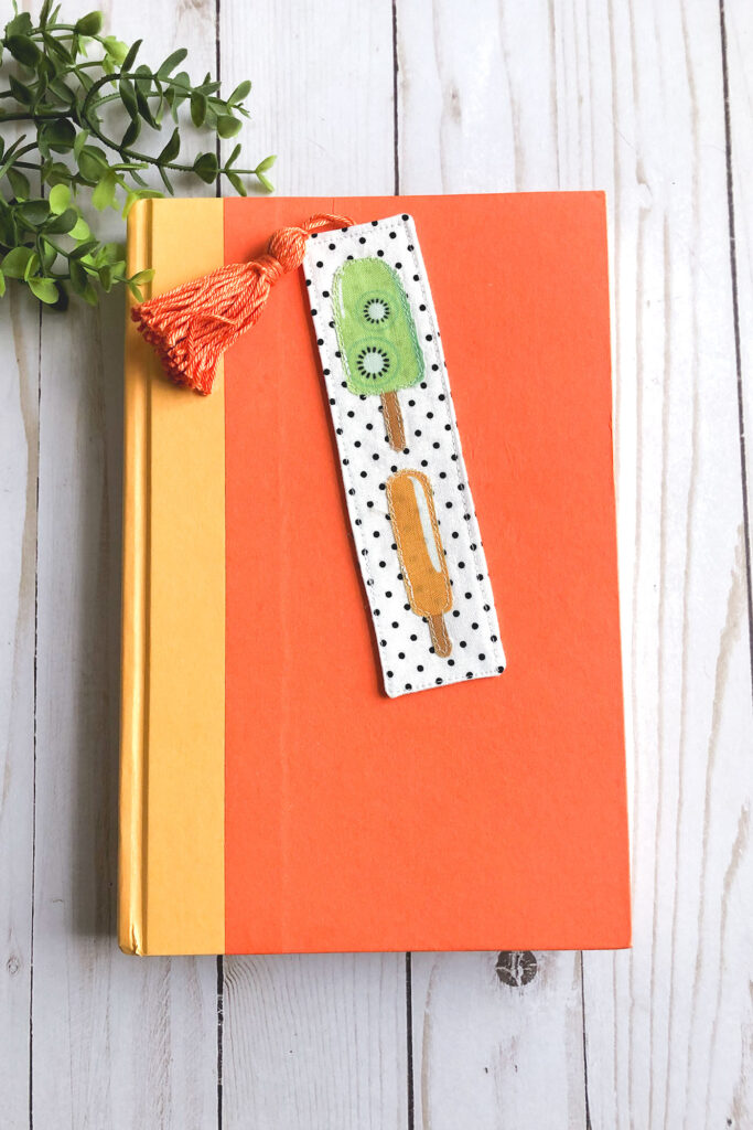 How to sew a tasseled fabric bookmark with top US sewing blog Ameroonie Designs. Image of bookmark with popsicle applique on a book.