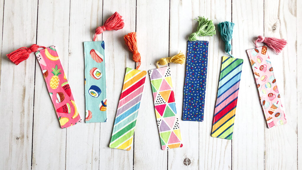 How to sew a fabric cover for a mini notebook with top US sewing blog Ameroonie Designs. Image of fabric bookmarks in rainbowfruit fabrics.