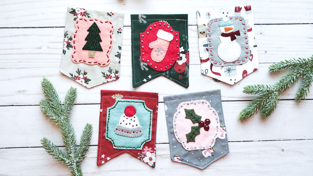 Gorgeous winter mini banner sneak peek with top US sewing blog Ameroonie Designs. Image of mini flags with wool felt applique in winter themes.