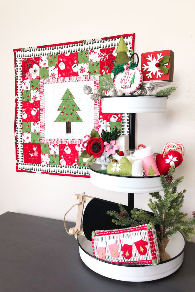How to sew a delightful holiday mini quilt by top US sewing blog Ameroonie Designs. Image of tiered tray with felt mittens, mini pillow and greenery.
