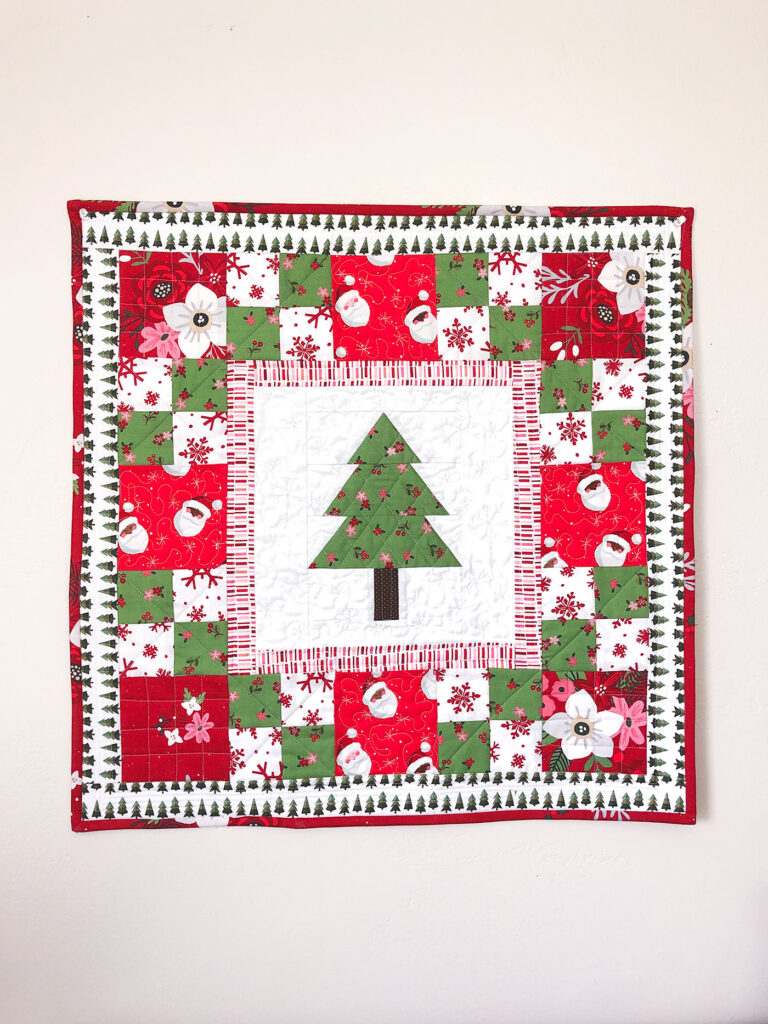 How to sew a delightful holiday mini quilt by top US sewing blog Ameroonie Designs. Image of mini quilt with pieced tree center block and red and green patchwork borders.