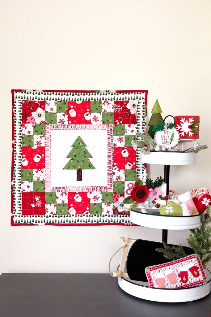 How to sew a delightful holiday mini quilt by top US sewing blog Ameroonie Designs. Image of holiday scene with mini quilt and decorated tiered tray.