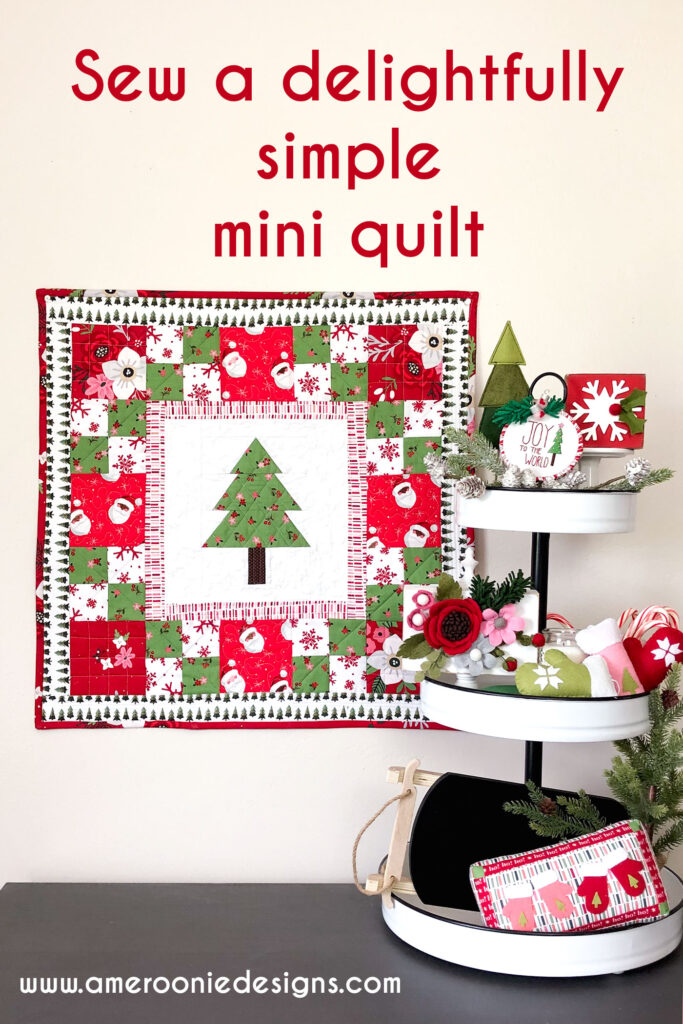 How to sew a delightful holiday mini quilt by top US sewing blog Ameroonie Designs. Image of mini quilt with tiered tray filled with mini pillows, greenery, felt flowers and more.