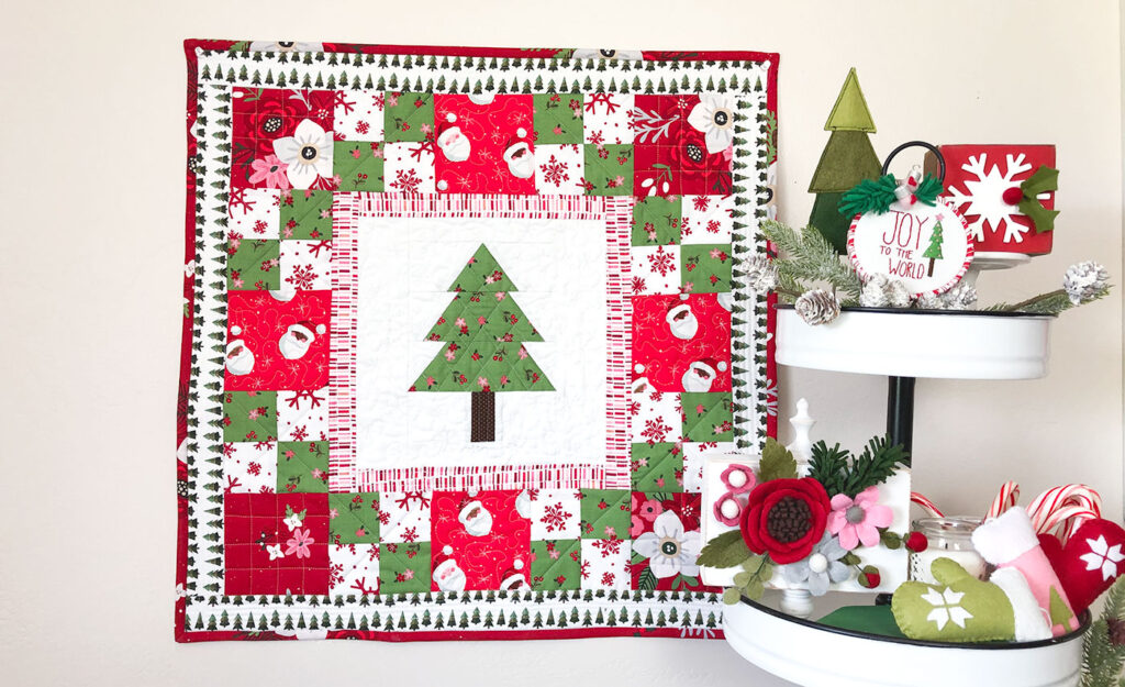 How to sew a delightful holiday mini quilt by top US sewing blog Ameroonie Designs. Image of mini quilt with tiered tray decorated with ornaments, wood blocks and felt embellishments.