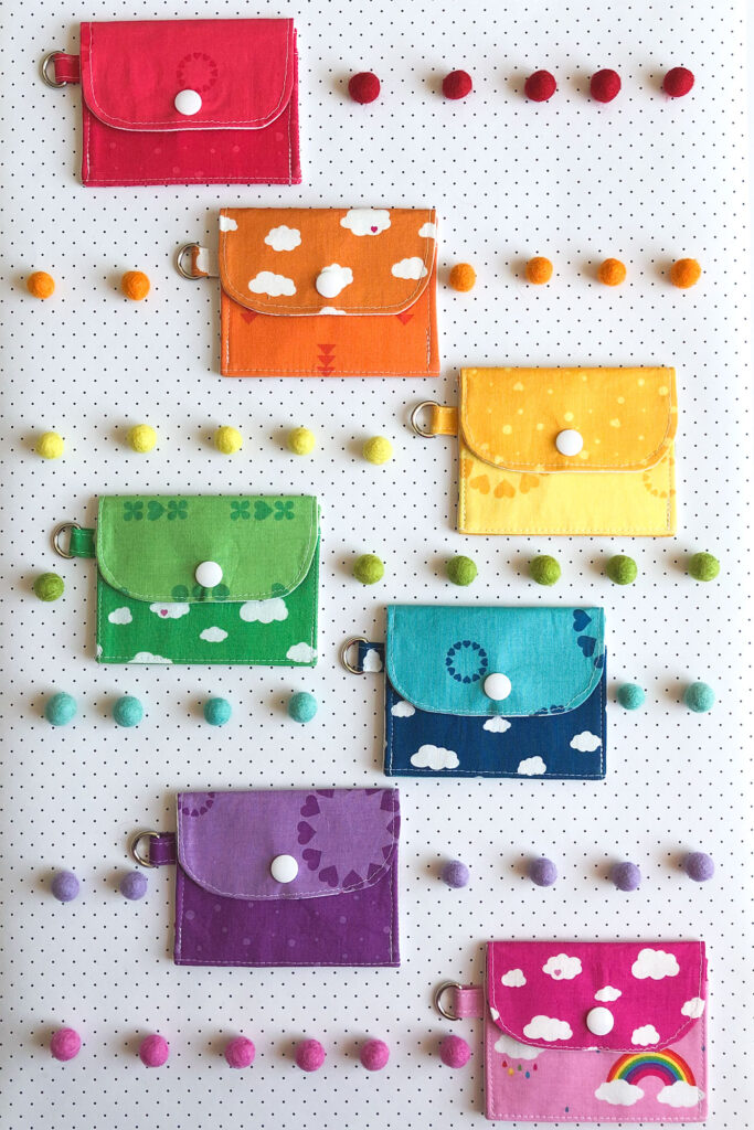 7 simple sewing projects to make this weekend from top US sewing blog Ameroonie Designs. Image of mini wallets in rainbow fabrics with felt poms.