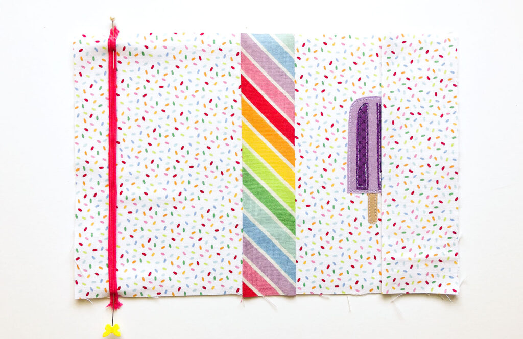 How to sew a fabric cover for a mini notebook with top US sewing blog Ameroonie Designs. Image of positioning elastic and sleeves on notebook cover.