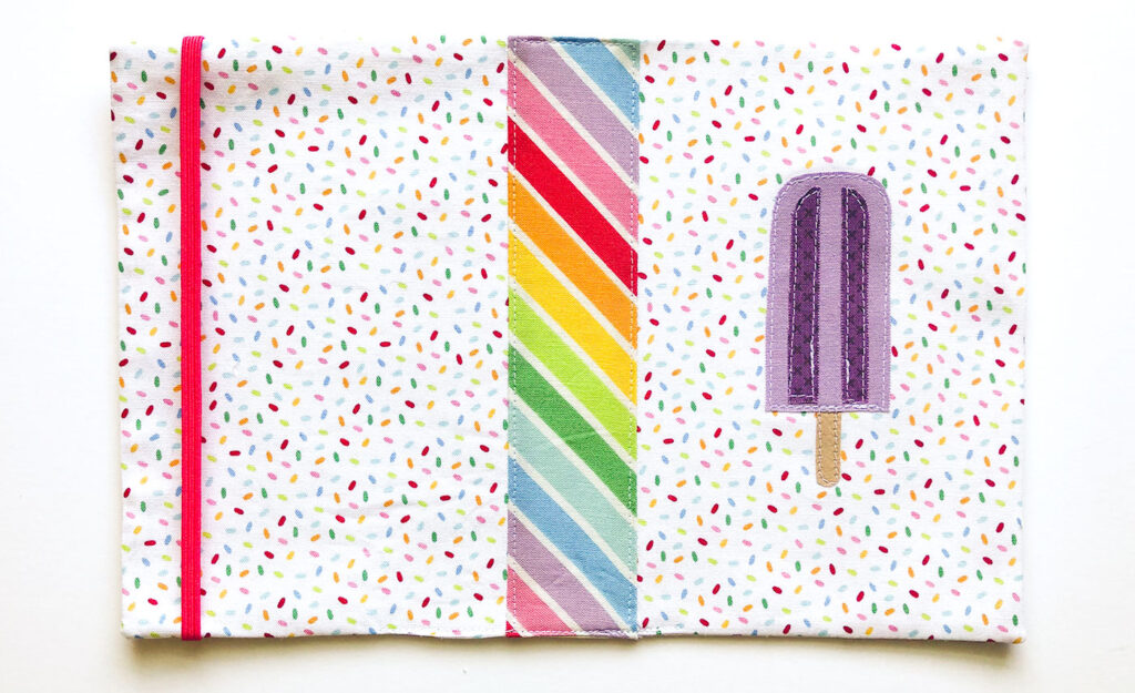 How to sew a fabric cover for a mini notebook with top US sewing blog Ameroonie Designs. Image of pressing and sewing closed notebook cover.