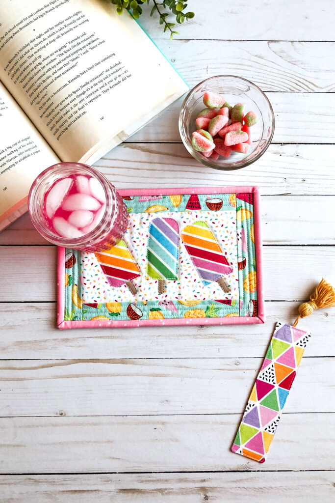 Free popsicle mug rug sewing tutorial with top US sewing blog Ameroonie Designs. Image of popsicle mug rug with book, drink and bookmark.
