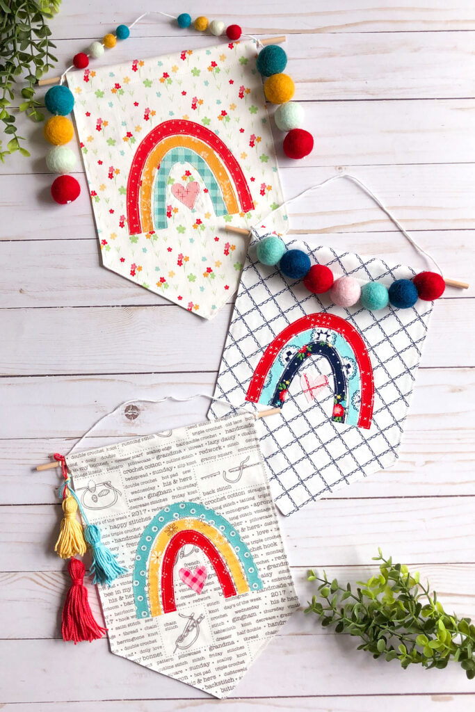 Sew your own colorful rainbow banner from top US sewing blog Ameroonie Designs. Image of fabric banners with rainbow applique and felt pom and yarn tassel embellishments.