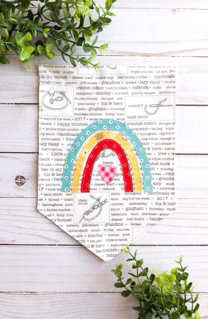 Sew your own colorful rainbow banner from top US sewing blog Ameroonie Designs. Image of sewn fabric banner.